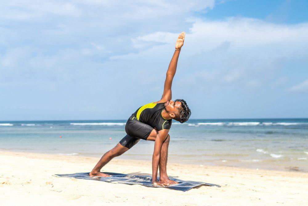 man-doing-yoga-pose-on-blue-mat-beside-seashore-616996